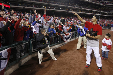 Philadelphia Phillies So Taguchi throws batting gloves to the fans after his team defeated the Tampa Bay Rays in Philadelphia