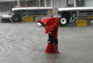 A man wades in floodwaters caused by continuous rains brought on by tropical storm Ketsana in Manila