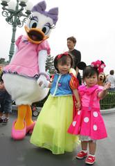 Japanese sisters meet Daisy Duck at Tokyo Disneyland in Urayasu.