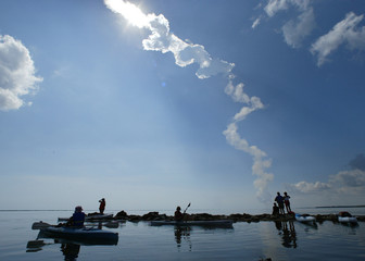 Spectators watch the space shuttle Discovery from their kayaks in Titusville, Florida.