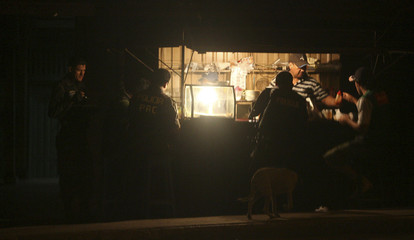 Members of the police eat at a kiosk before the start of a curfew in Cobija