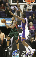 Milwaukee Bucks Mo Williams passes to a teammate while being guarded by Phoenix Suns Amare Stoudemire during fourth quarter NBA basketball action in Phoenix