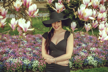 Beautiful girl with black hair in a black dress on a background of a magnolia flower. Blurring background. Shooting outdoors. The concept of fashion and beauty. Beautiful girl and magnolia flowers.