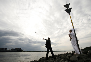 Bride and Groom throw a message in a bottle shortly after their wedding at the banks of the Elbe river near Hamburg