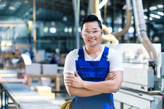 Worker in his carpenter workshop standing proud