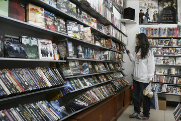 A customer looks at pirated DVDs displayed at a shop in Beijing