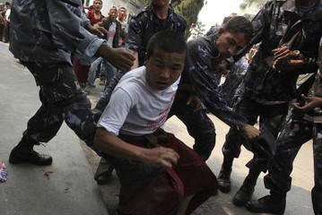Police beat a Tibetan protester during a pro-Tibet demonstration in Kathmandu