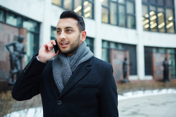 Portrait of stylish Middle-Eastern businessman speaking by phone against background of modern building in city