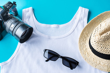 Travel kit: hat, camera, t-shirt and sun glasses. Flat lay composition for social media and travelers. overhead view