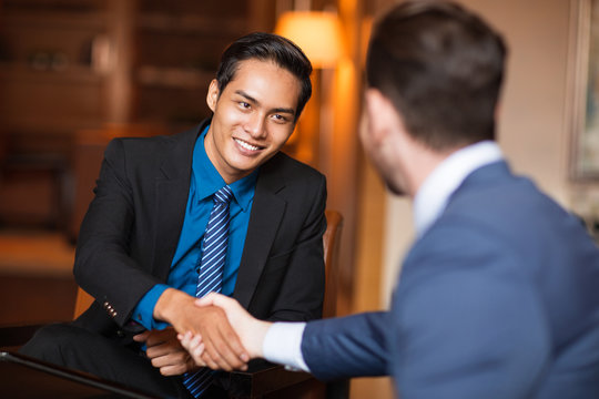 Two Smiling Business Partners Shaking Hands