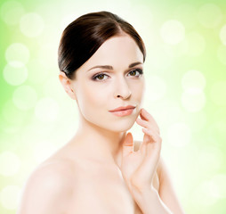 Portrait of young, beautiful and healthy woman: over green background. Healthcare, spa, makeup and face lifting concept.