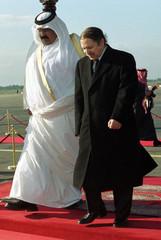 ALGERIAN PRESIDENT BOUTEFLIKA WALKS WITH QATARI RULER WHO ARRIVES FOR TALKS.