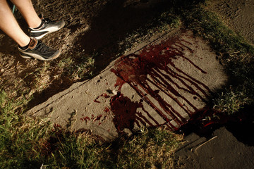 Resident stands next to bloodstains of man who was gunned down by unknown assailants in border city of Ciudad Juarez