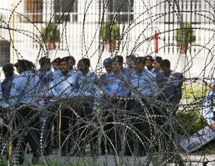 Pakistani policemen stand guard behind the barbwire outside the Election Commission in Islamabad
