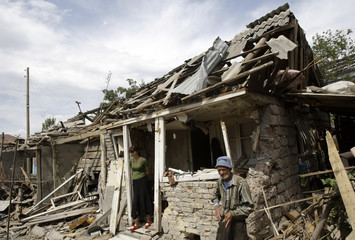 A South Ossetian family stand outside their house which was destroyed by a Georgian strike in Tshinvali