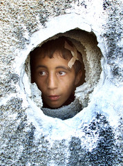 WOUNDED HUSSEIN ABU TAHA, 10, LOOKS THROUGH A HOLE MADE BY AN ISRAELITANK SHELL IN A RELATIVES' ...