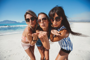 Beautiful young women blowing kisses on the beach