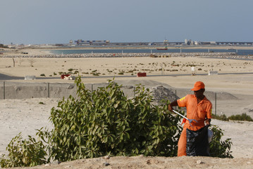 A man works on UAE's national day holiday as suspended work on Nakheel's Palm Jebel Ali is seen in the background in Dubai
