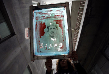 A worker washes ink from a screen print at a shirt printing factory located on the outskirts of Beijing