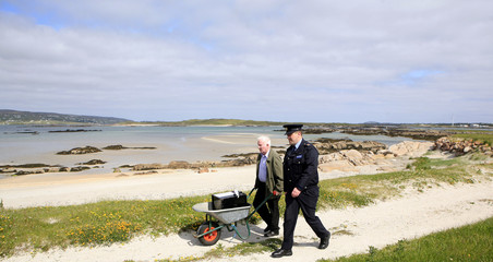 Gardai Mulkearns and presiding officer O'Donnell wheel the ballot box from the harbour to the polling station, on the island of Inishfree