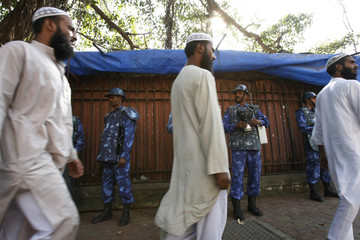 Indian Muslim walk past Indian paramilitary personnel during 'Justice Rally' in Mumbai