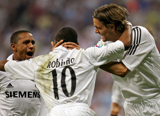 Real Madrid's Robinho is congratulated by team mates Carlos and Woodgate after scoring against Athletic Bibao during their Spanish First Division soccer match in Madrid