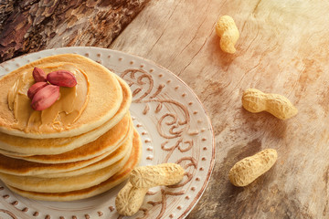 Stack of hot pancakes with peanut butter