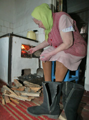 An eldery woman stokes the fire in her kitchen's oven in the eastern Ukrainian city of Donetsk