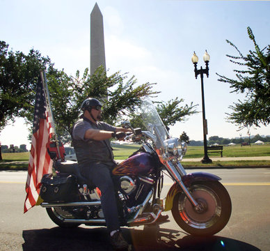 MAN RIDES MOTORCYCLE WITH AMERICAN FLAG.