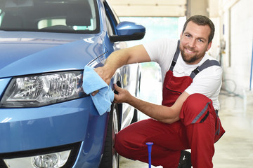 professionelle Autoreinigung in einer Werkstatt - Mann poliert Lack eines Fahrzeuges // Professional car cleaning in a workshop - man polishing paint of a vehicle