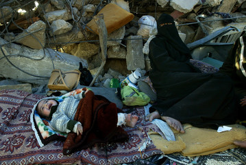 A Palestinian homeless with her baby sits inside a tent after her house was demolished at the Khan ...