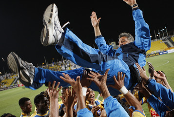 Players and staff throw Al-Gharafa's head coach Castro into the air as they celebrate winning the Qatar Stars League in Doha