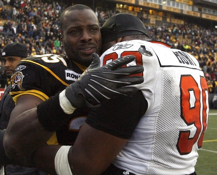 Tiger-Cats linebacker Otis Floyd is consoled by B.C. Lions defensive tackle Aaron Hunt during their CFL Eastern semi-final football game in Hamilton