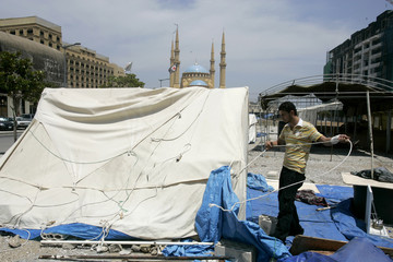 A member of Lebanon's Hezbollah-led opposition remove a tent from central Beirut