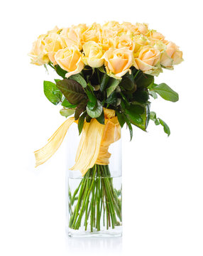 Bouquet of yellow roses in glass vase over white