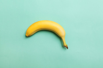 ripe banana on a background of mint color