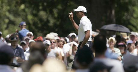 Woods of the U.S. waves after sinking a birdie putt on the first hole during the second round of the 89th PGA Championship golf tournament at Southern HIlls Country Club in Tulsa