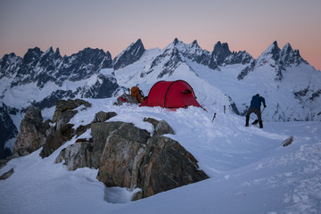 Man shoveling snow at sunset by campsite and mountains, North Cascade, Beckler Peak, Washington, USA