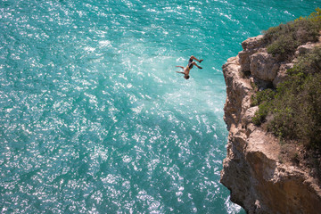 Man jumping upside down from cliff to sea, full frame