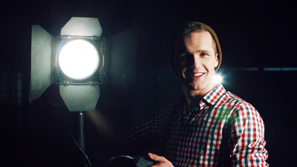 Stylish man in hat and standing at studio light stand with switcher in hand, turning it on and checking and smiling, looking at camera