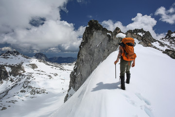 Man hiking in snow by mountains,rear view, The Enchantments, Washington, USA