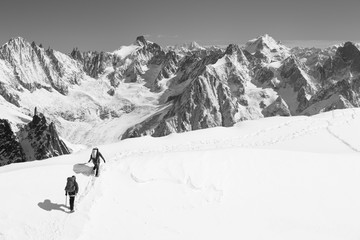 Two people hiking in snow by mountains, black and white