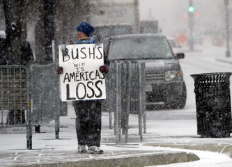 A lone demonstrator holds a sign protesting the election of U.S. President George W. Bush near the W..