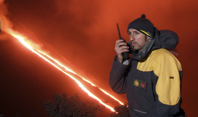 A Guardia di Finanza corporal speaks on his radio as lava flows towards the sea from a hillside on the volcanic Italian island of Stromboli