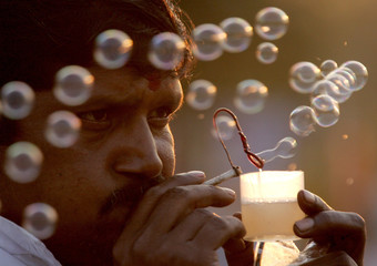 An Indian vendor makes soap bubbles from an improvised pipe in New Delhi.