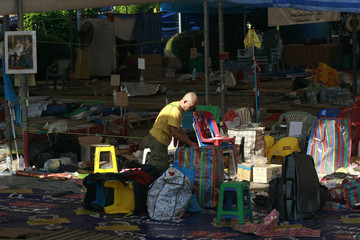 An anti-government demonstrator packs equipment used in rallies at Government House in Bangkok