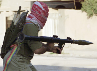 MASKED IRAQI INSURGENT ARMED WITH A ROCKET PROPELLED GRENADE RUNS TO A POSITION DURING CLASHES IN FALLUJA.