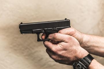 Hands Holding Gun with Finger on Trigger