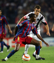 Barcelona's Eto'o fights for the ball with Udinese's Zenoni during their Champions League match at Nou Camp Stadium in Barcelona