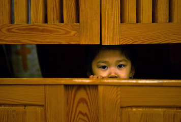 Vietnamese girl peeks out from a confession booth during a mass for Vietnamese immigrants in Poland
